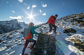 Hiker helping partner on mountain trail. Snowcapped rocky mountains in Canada.