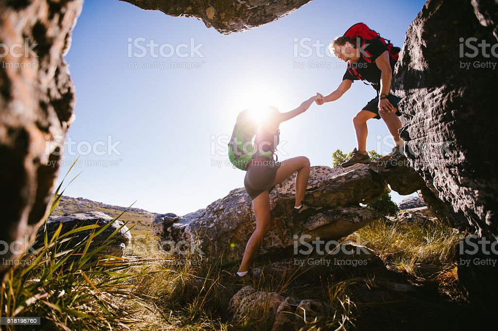 Hiker helping woman climbing rock while hiking in nature stock photo