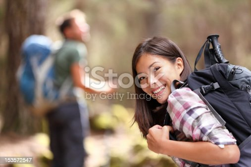 Hiking. xwoman hiker smiling in forest with male hiker in the background. Mixed-race Asian Caucasian female model happy. From Aguamansa, Tenerife, Spain