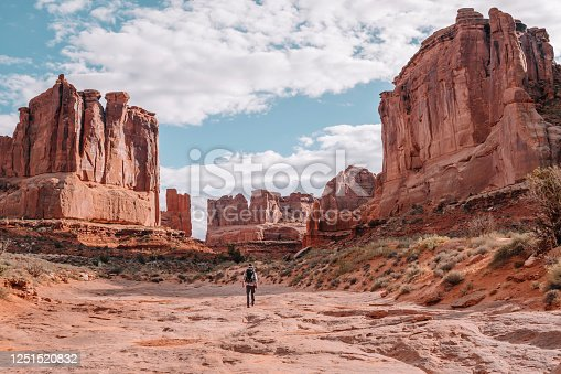 A hiker in the scenic landscape of Park Avenue in Arches National Park, Moab, Utah, USA. Red rocks and desert landscape with scrub brush under blue sky with fluffy clouds.