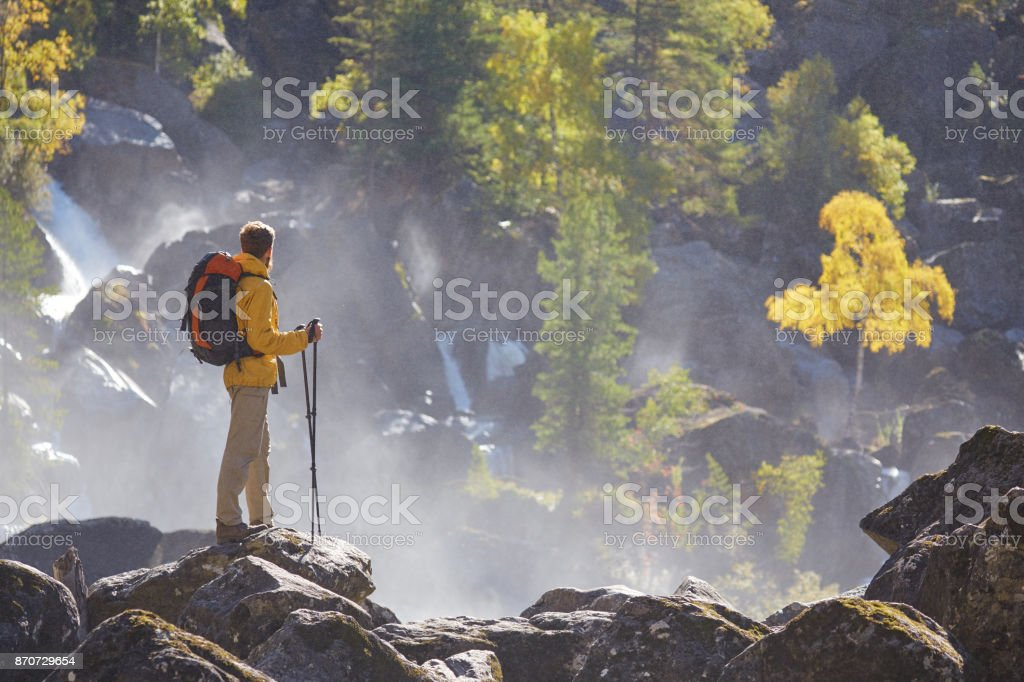 Hiker hiking with backpack looking at mountain river stock photo
