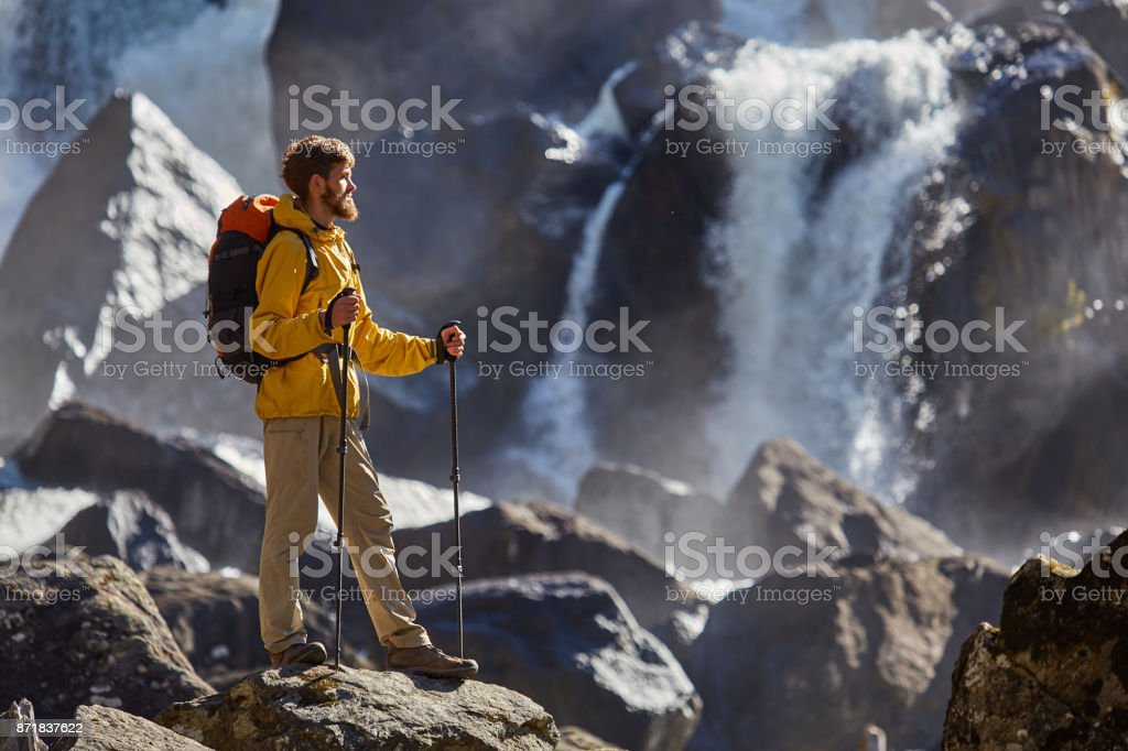 Hiker hiking with backpack looking at waterfall stock photo