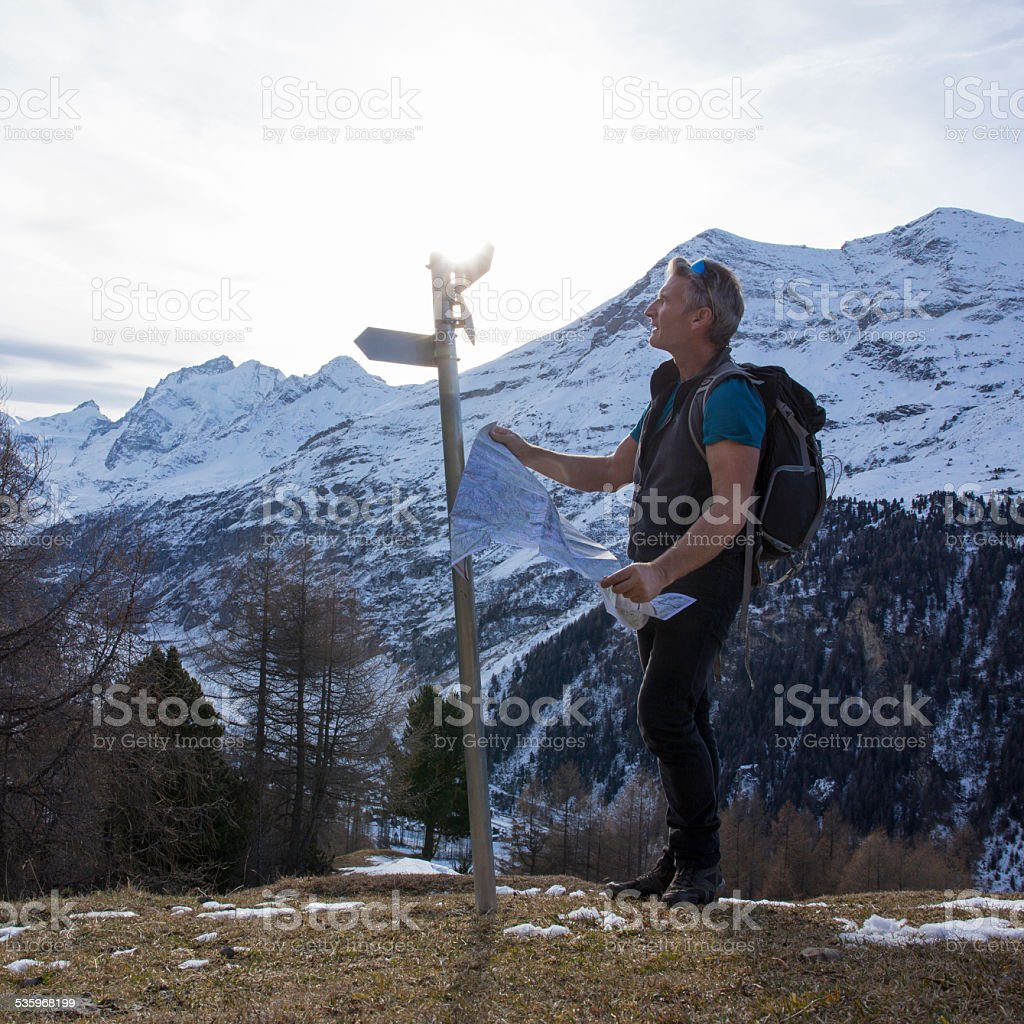 Hiker holds map, looks at directional sign stock photo