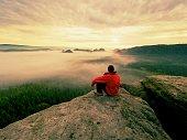 istock Hiker in black on the rocky peak. Wonderful daybreak in mountains, heavy orange mist in deep valley. 923473022