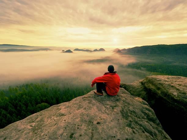 Hiker in black on the rocky peak. Wonderful daybreak in mountains, heavy orange mist in deep valley. stock photo