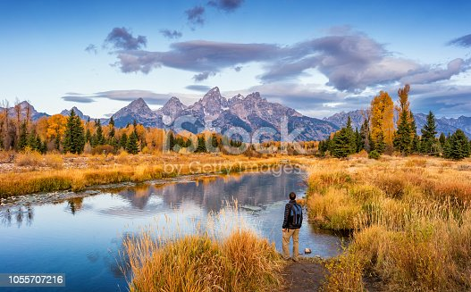 Stock photograph of hiker looking at view at Schwabacher Landing in Grand Teton National Park, Wyoming, USA, at dawn.
