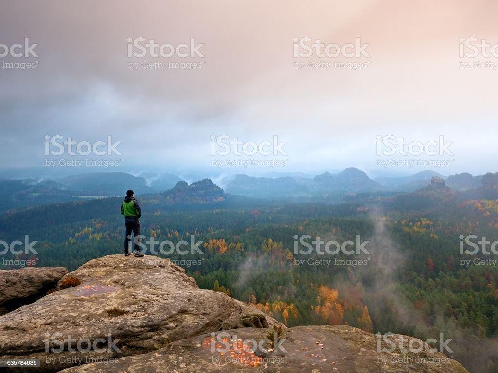 Hiker in green windcheater stand on mountain peak stock photo