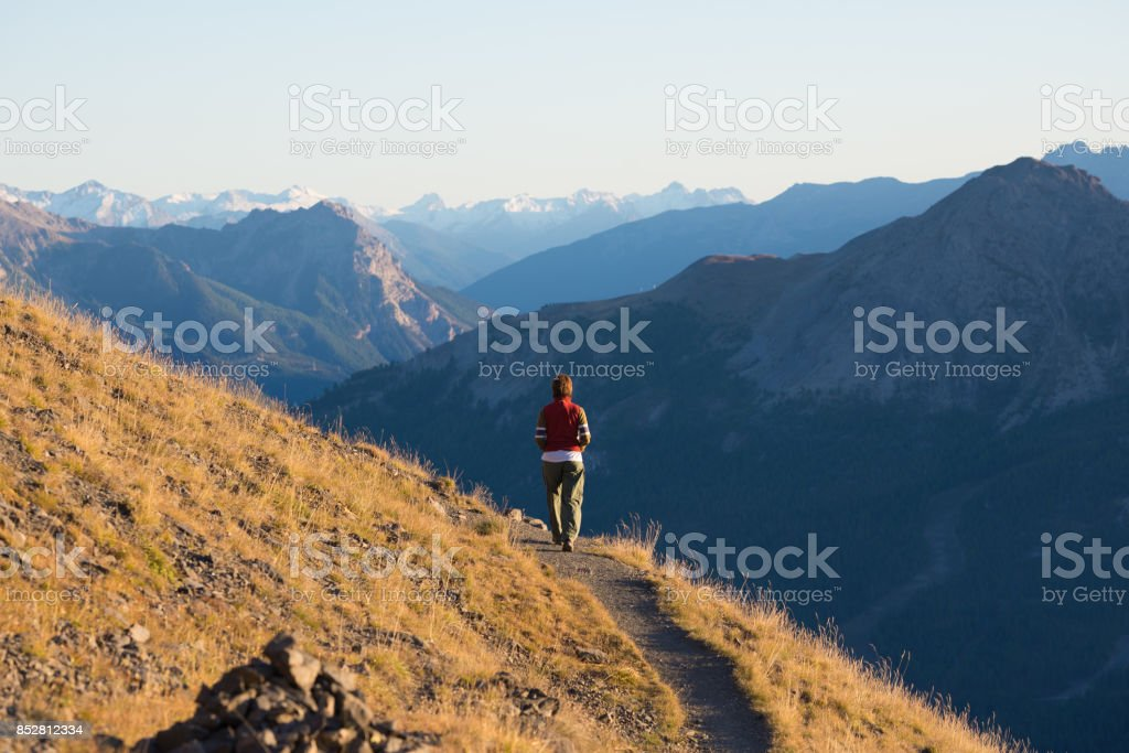 Hiker in high altitude rocky mountain landscape. Summer adventures on the Italian French Alps, toned image. stock photo