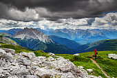 COMELICO SUPERIORE / ITALY - JULY 3, 2017: Hiker in red coat and hat takes photos of jagged Crode dei Longerin peak of Alpi Carniche range in Belluno, Veneto, on Karnischer Hohenweg or Traversata Carnica long distance trail on Austrian border