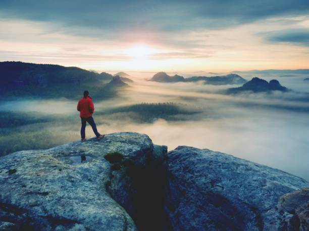 Hiker in red jacket enjoy view over clouds. Mountain rocky peak stock photo