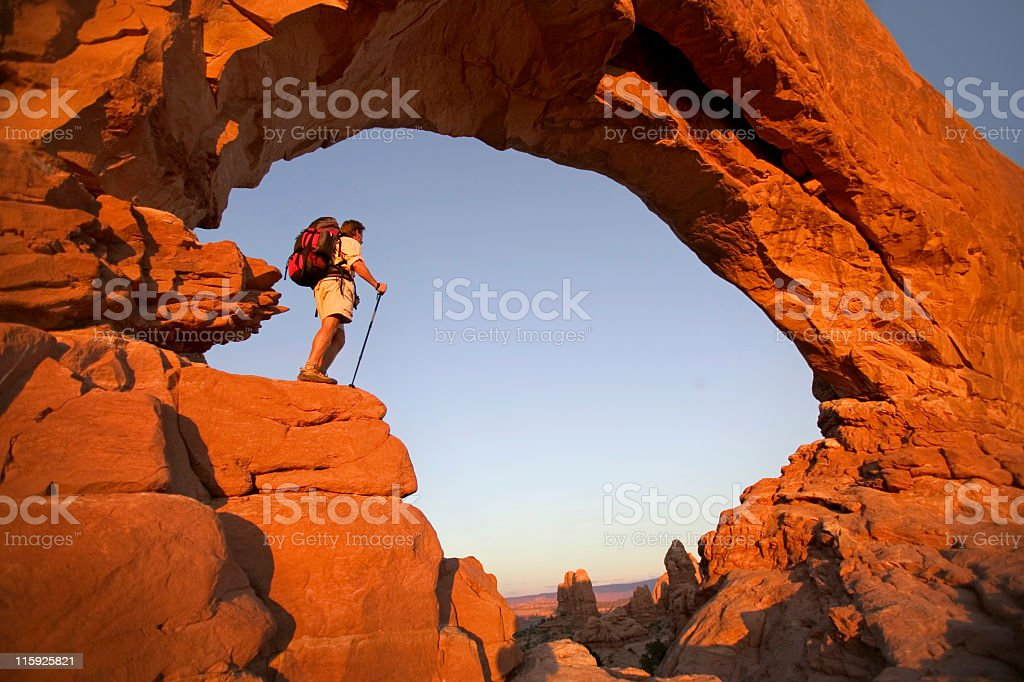 Hiker in Rock Arch Looking at View stock photo