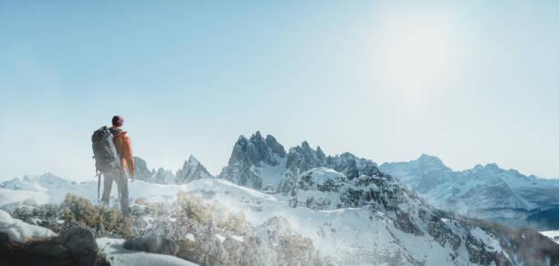 hiker in snowy mountain landscape - alpinismo foto e immagini stock