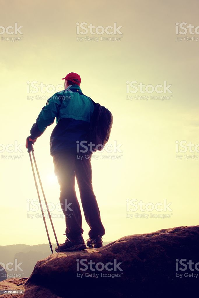 Hiker in windcheater, baseball cap and with trekking poles stock photo