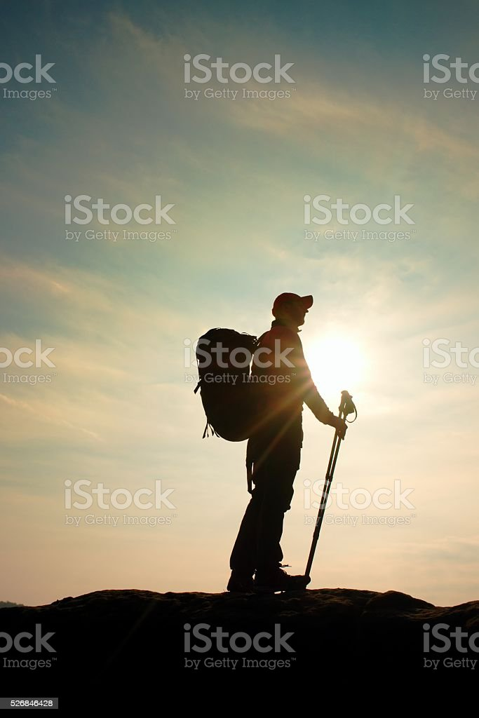 Hiker in windcheater, baseball cap and with trekking poles stand stock photo