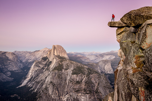 A fearless male hiker is standing on an overhanging rock at Glacier Point enjoying the breathtaking view towards famous Half Dome in beautiful post sunset twilight in summer, Yosemite National Park, California