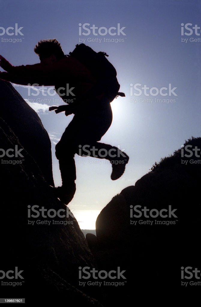hiker jumping from rock to rock royalty-free stock photo