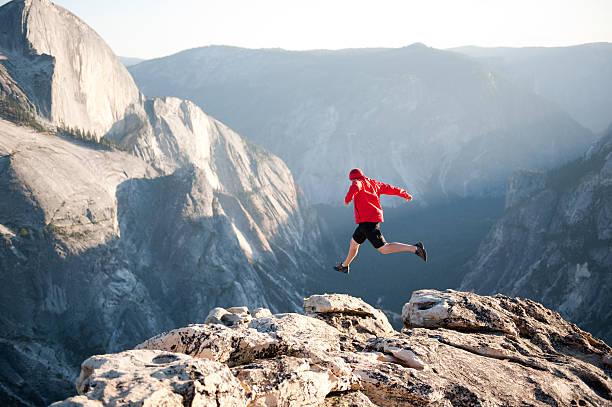 Hiker jumping the gap stock photo