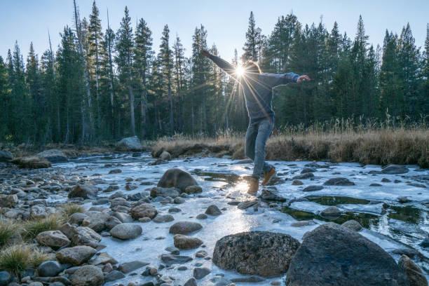 Wanderer springt von Felsen zu Felsen übergefrorenen Fluss bei Sonnenuntergang in Pinienwald – Foto