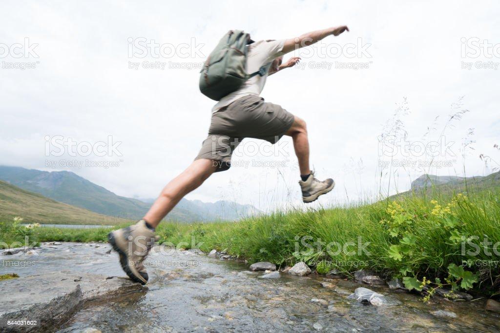 Wanderer springt über Fluss – Foto