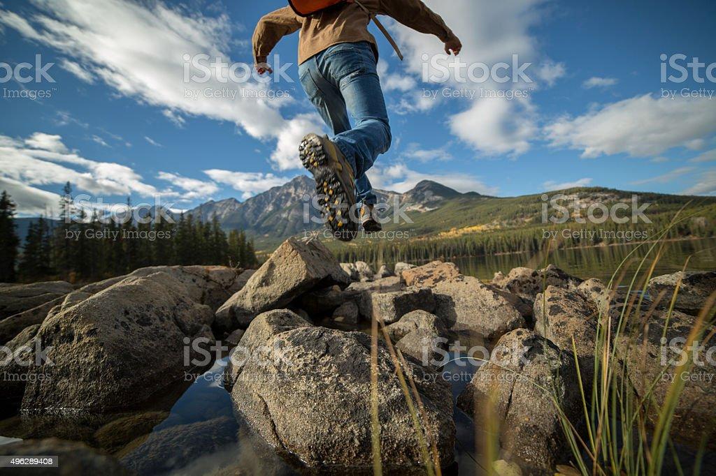 Wanderer springen rock für rock in mountain lake entfernt. Low Winkel – Foto