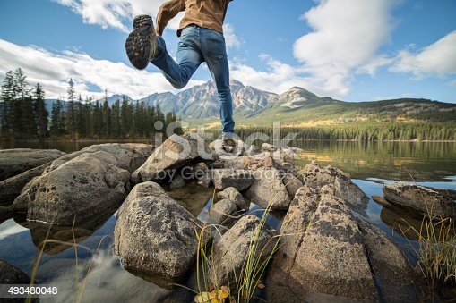 istock Hiker jumps rock to rock in mountain lake 493480048