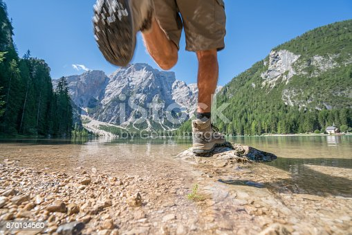 Young male hiker jumping from rock to rock on mountain lake in Summer.