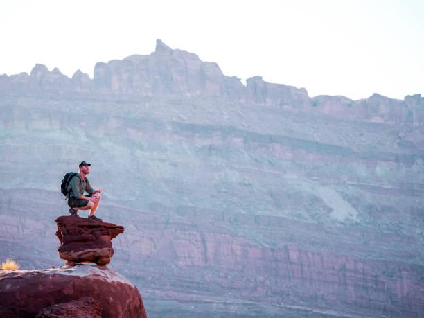 Hiker kneels on rock stock photo