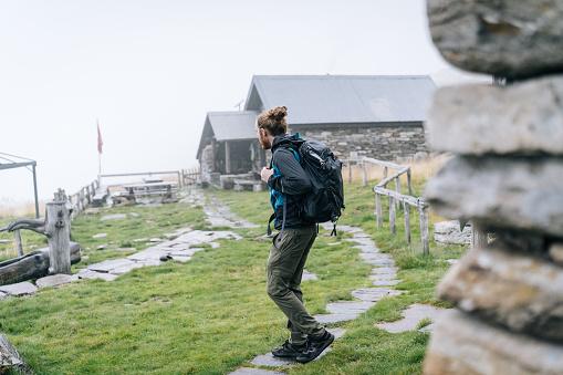 Hiker leaves cabin in mountain meadow
