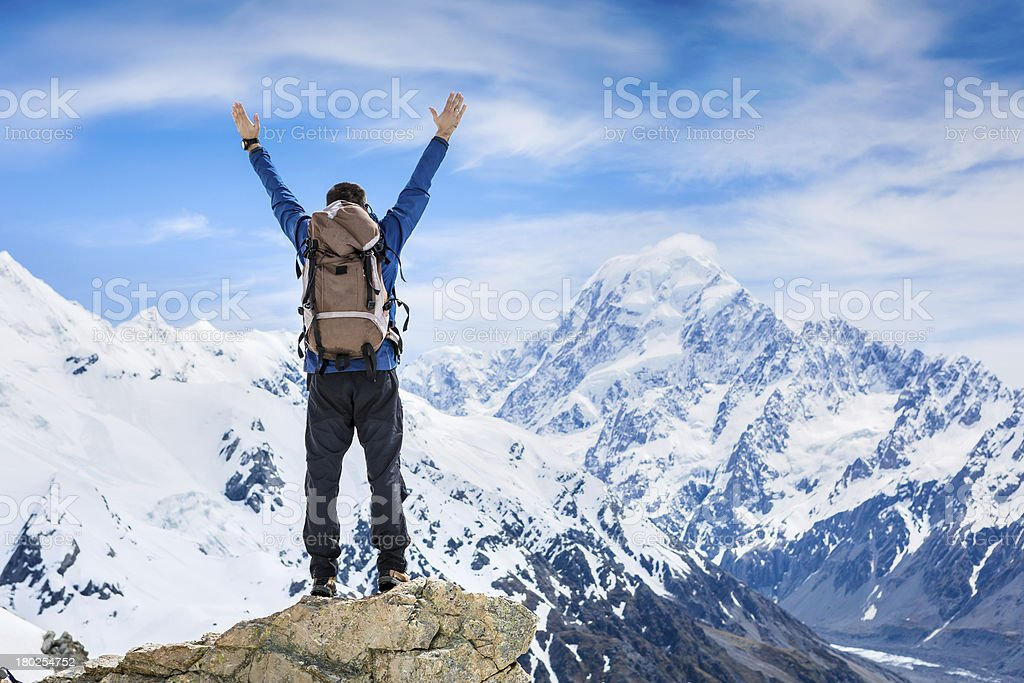 hiker lifts his arms in victory royalty-free stock photo