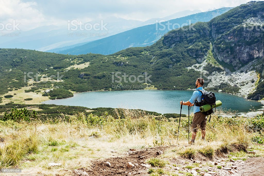 Hiker looking at majestic mountain scenery stock photo