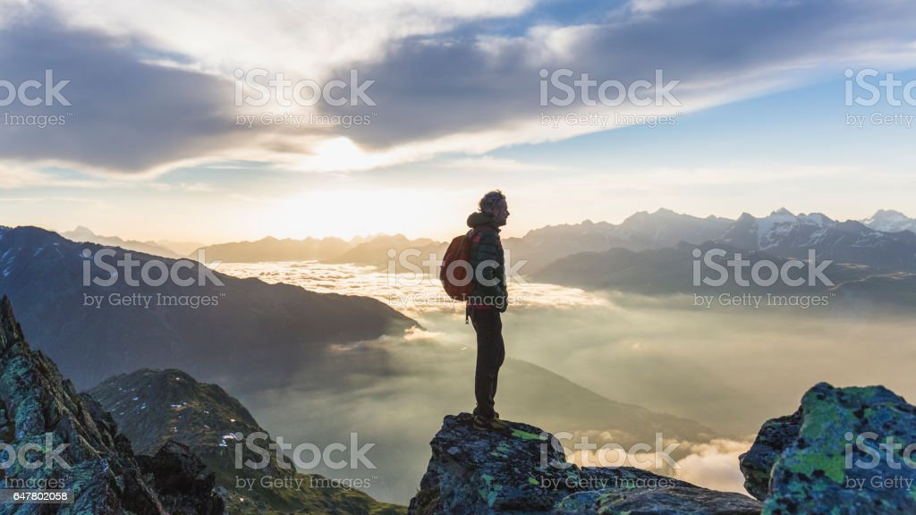 Hiker looking at mountain range stock photo