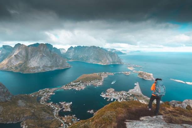 Alpinista, olhando para a vista de Reine em Lofoten, Noruega - foto de acervo