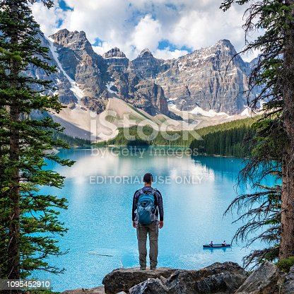 Banff National Park, Alberta, Canada - July 19, 2018: Hiker looking at view at Moraine Lake in Banff National Park, Canadian Rockies, Alberta, Canada.