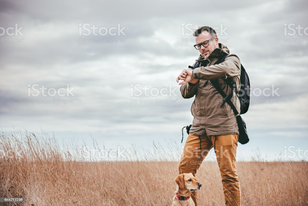 Hiker looking at watch stock photo