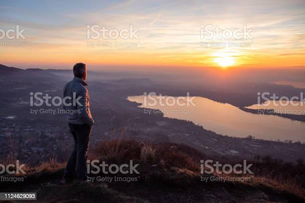 Photo of Hiker looking sun over horizon