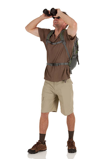 Hiker looking through binoculars stock photo