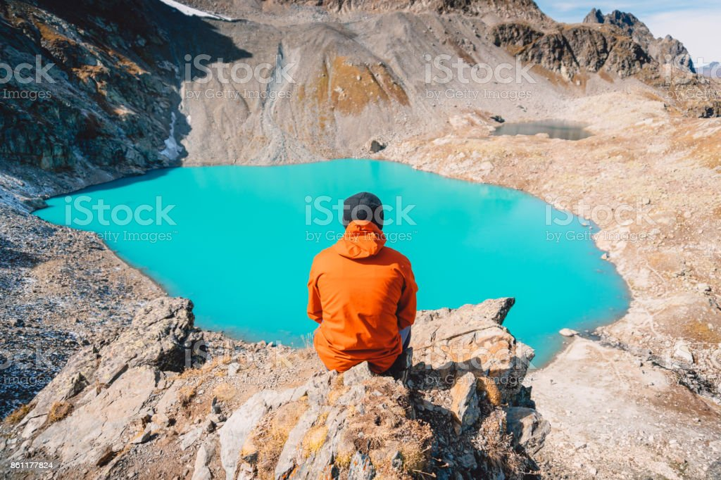 Hiker looks at the mountain lake from a height. Beautiful turquoise lake in the mountains. stock photo