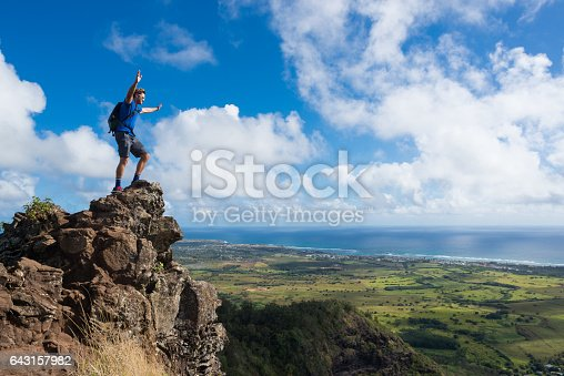A hiker on top of the rocks with hands raised celebrating the beauty.