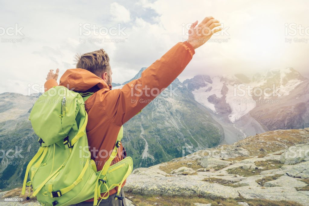 Hiker male arms outstretched on mountain top, Switzerland stock photo