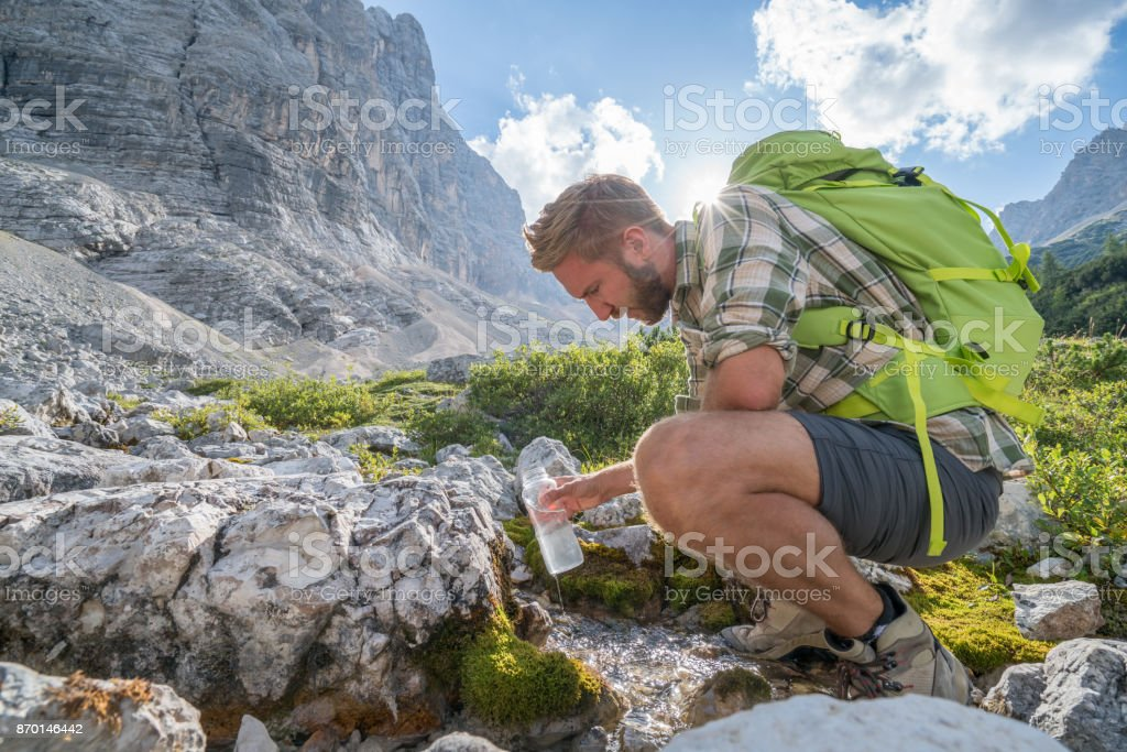 Young man hiker on trail in Summer refreshing from water bottle