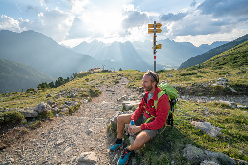Hiker male resting on trail in beautiful nature environment in the Swiss alps