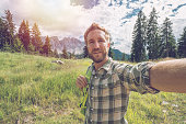 Young man taking a selfie portrait in the Dolomites in Alto Adige region, Italy.