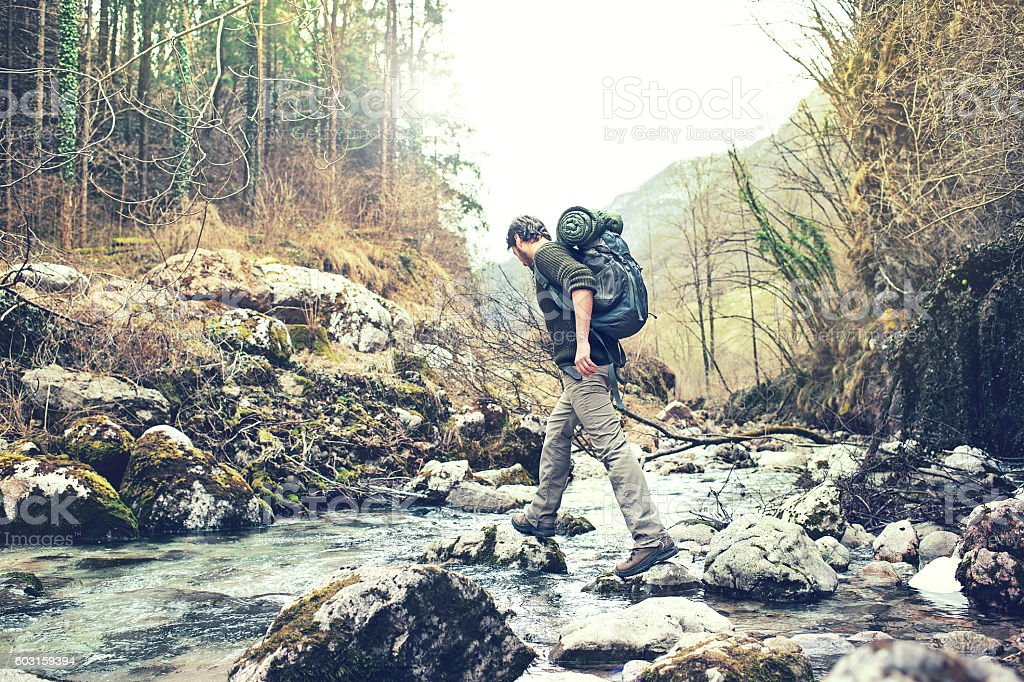 hiker man crossing the river to reach the other side stock photo