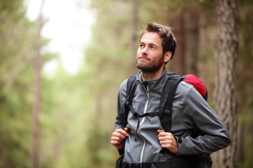 Hiker - man hiking in forest. Male hiker looking to the side walking in forest. Caucasian male model outdoors in nature. Click for :