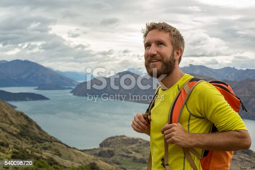 istock Hiker man stands on mountain top and looks at view 540098720
