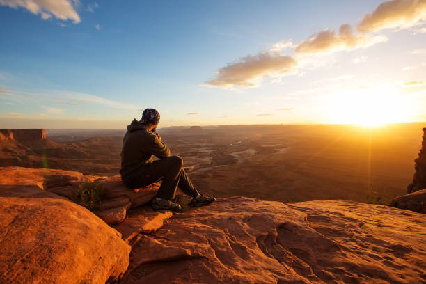 Wanderer trifft Sonnenuntergang am Grand Aussichtspunkt im Canyonlands National Park in Utah, USA – Foto
