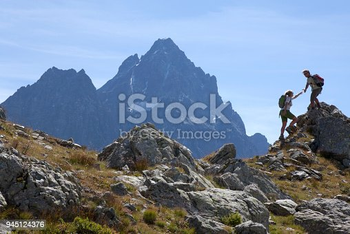 istock Hiker offers hand to companion, on mountain ridge, Piedmont, Italy 945124376
