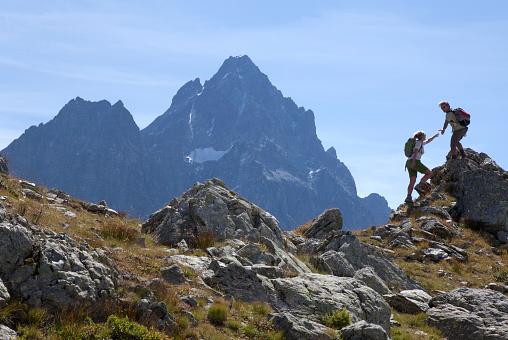 istock Hiker offers hand to companion, on mountain ridge, Piedmont, Italy 945124376