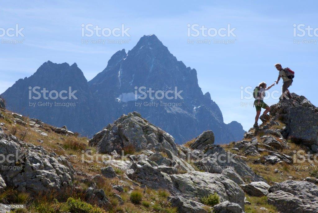 Hiker offers hand to companion, on mountain ridge, Piedmont, Italy stock photo