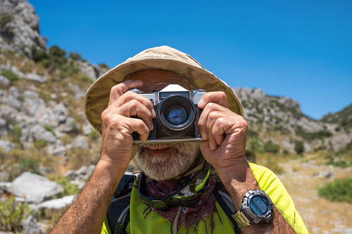 60 year old man in yellow shirt. In Safari hat. With backpack. He takes pictures with an analog camera in his hand. In nature. He has a wrist watch. Lunch time close-up portrait